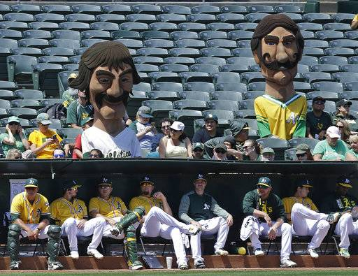 Oakland Athletics' mascots representing former A's pitchers Dennis Eckersley upper left, and Rollie Fingers sit with fans above the bullpen in the fourth inning of a baseball game against the Baltimore Orioles, Sunday, Aug. 13, 2017, in Oakland, Calif. (AP Photo/Ben Margot)