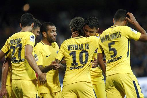 PSG's Neymar, center right back to camera, is congratulated by teammates Dani Alves after scoring his side's 3rd goal during the French League One soccer match between Guingamp and PSG at the Roudourou stadium in Guingamp, western France, Sunday, Aug. 13, 2017. Neymar makes his long-awaited debut with Paris Saint-Germain on Sunday in the small Brittany town of Guingamp. (AP Photo/Kamil Zihnioglu)