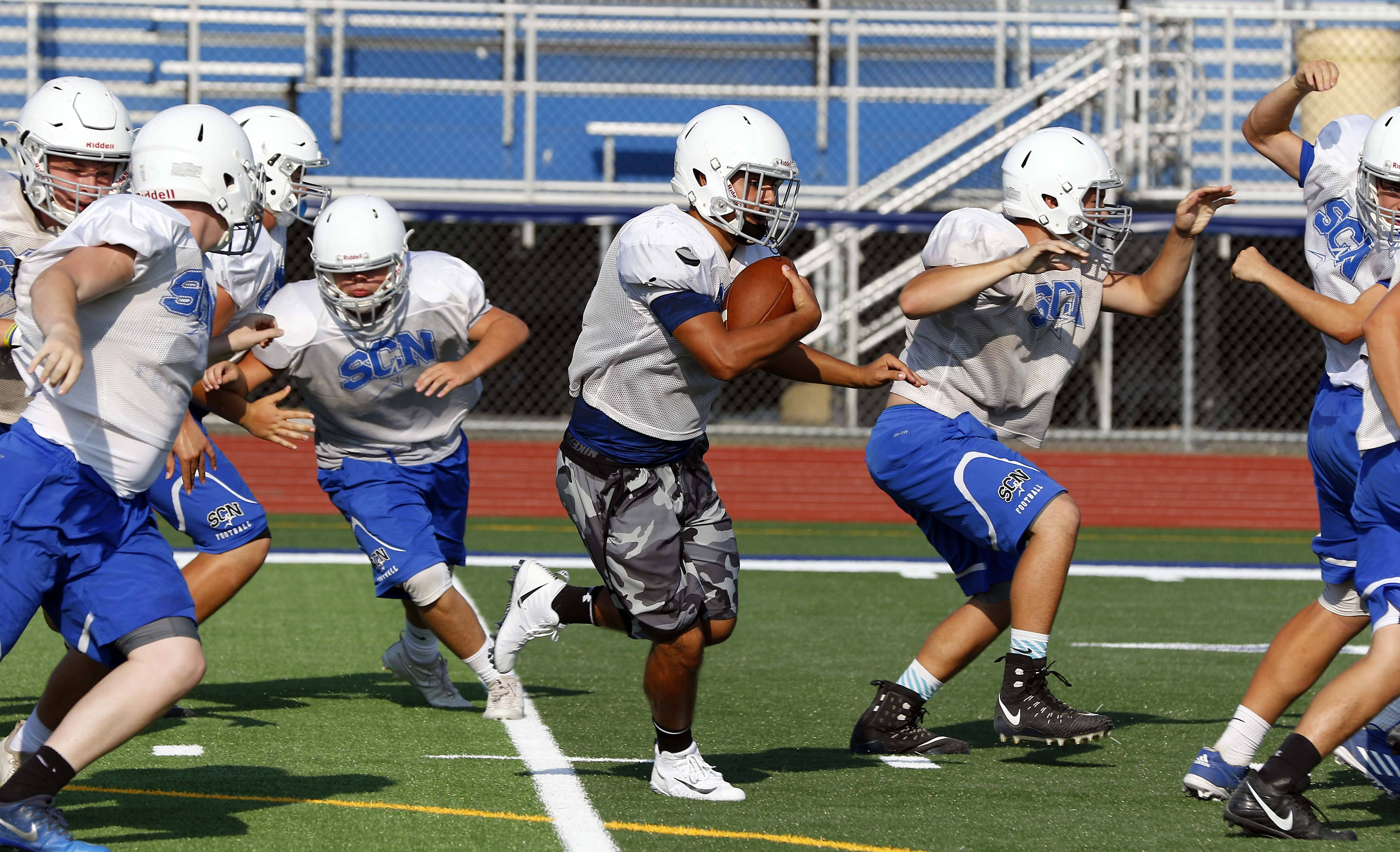 Sam Demarco works his way upfield with the ball during St. Charles North football practice.
