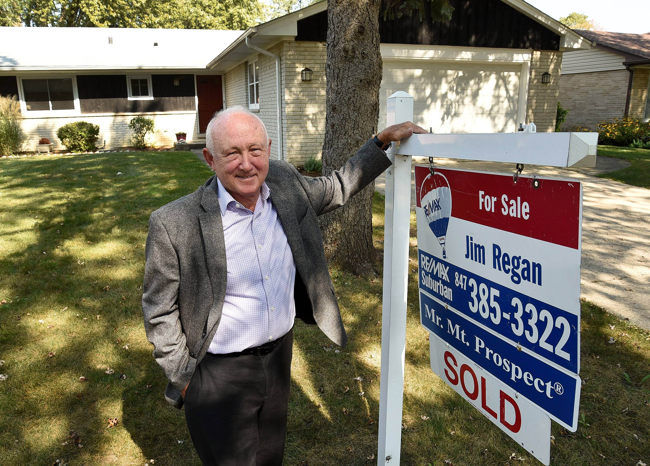 Jim Regan, RE/MAX Suburban, next to his sign in front of one of his listings in Mount Prospect.