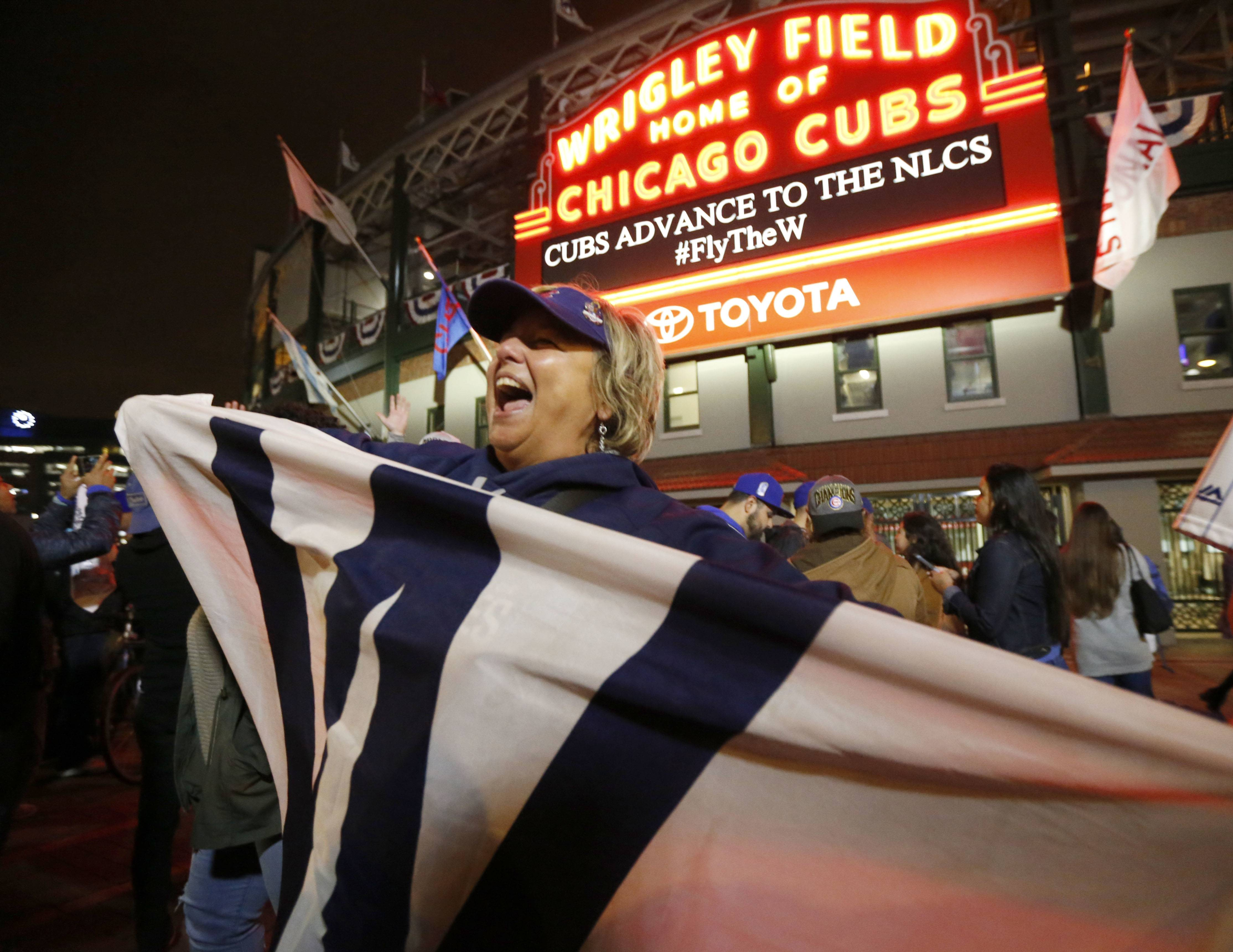 Cubs fans celebrate outside Wrigley Field on Thursday in Chicago, after the Cubs defeated the Washington Nationals 9-8 in Washington in Game 5 of the National League division series to advance to the NLCS.