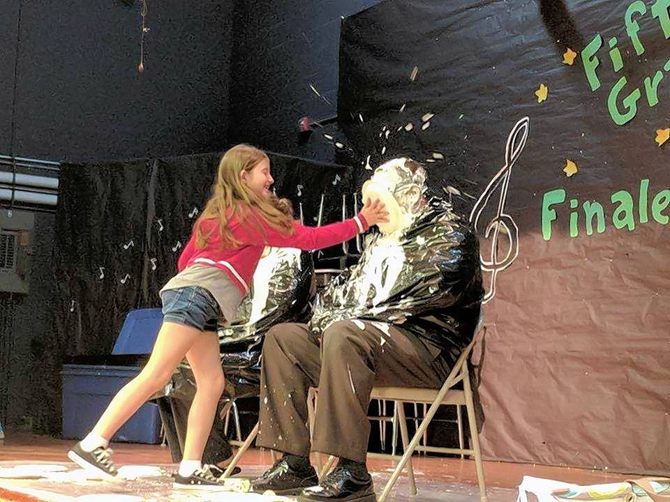 Hampshire Elementary School third-grader Albina Ramadani delivers a pie to the face of Community Unit District 300 Superintendent Fred Heid during a recent fundraiser supporting hurricane relief. Students, employees and families collected nearly $34,000 over two weeks.