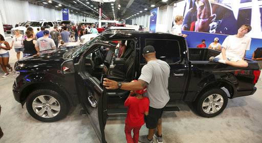 In this Monday, Oct. 9, 2017, photo, fairgoers look at pickup trucks on display at the State Fair of Texas in Dallas. America's favorite luxury vehicle is a pickup truck. Buyers are increasingly outfitting their pickups with all the comforts of luxury cars, from heated and cooled seats to backup cameras to panoramic glass roofs. (AP Photo/LM Otero)