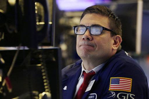 The screens of specialist Robert Tuccillo are reflected in his glasses as he works at his post on the floor of the New York Stock Exchange, Thursday, Oct. 12, 2017. Stocks are opening slightly lower on Wall Street, a day after setting their latest record highs. (AP Photo/Richard Drew)