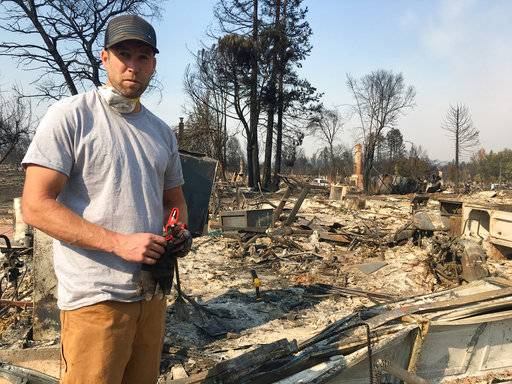 Resident Ryan Nelson goes through the ruins of his house to try to find his grandfather's rifles in Santa Rosa, Calif., Wednesday, Oct. 11, 2017. As his house filled with smoke from one of California's devastating wine country fires, Nelson's thoughts went to his elderly neighbors, one of whom has multiple sclerosis. He ran over and pounded on their doors and windows, but wasn't able to get their attention. Now he fears they didn't make it out and wonders whether he could have done more to help. (AP Photo/Jonathan Copper)