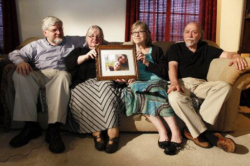 FILE - In this June 4, 2014, file photo, from left, Patrick Boyle, Linda Boyle, Lyn Coleman and Jim Coleman hold photo of their kidnapped children, Joshua Boyle and Caitlan Coleman, who were kidnapped by the Taliban in late 2012, Wednesday, June 4, 2014, in Stewartstown, Pa. Pakistan's military says soldiers have recovered five Western hostages held by the Taliban for years. Pakistan's army did not name those held, only saying it worked with U.S. intelligence officials to track down the hostages and free them after discovering they had been brought into Pakistan. (AP Photo/Bill Gorman, File)
