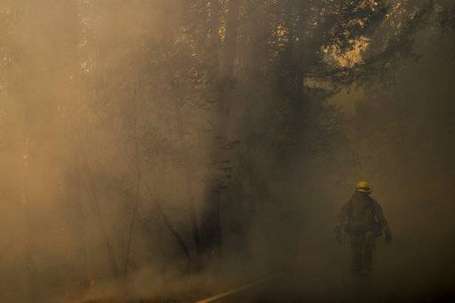 A firefighter walks along the Highway 29 as thick smoke from a wildfire fills the air Thursday, Oct. 12, 2017, near Calistoga, Calif. Officials say progress is being made in some of the largest wildfires burning in Northern California but that the death toll is almost sure to surge.