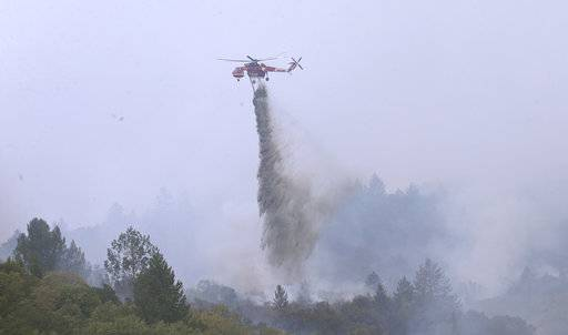 A helicopter drops a load of water on a wildfire Thursday, Oct. 12, 2017, in Sonoma, Calif. Gusting winds and dry air forecast for Thursday could drive the next wave of devastating wildfires that are already on their way to becoming the deadliest and most destructive in California history.