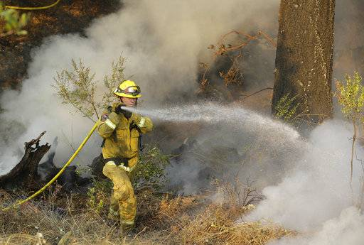 A Cal Fire firefighter works on hot spots on a hill in the Oakmont area of Santa Rosa, Calif., Thursday, Oct. 12, 2017.  A forecast for gusty winds and dry air threatened to fan the fires, which are fast becoming the deadliest and most destructive in California history after destroying thousands of homes and businesses. .