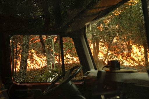 A wildfire burning along the Highway 29 is seen through a fire truck Thursday, Oct. 12, 2017, near Calistoga, Calif. More than 8,000 firefighters are battling the blazes and additional manpower and equipment was pouring in from across the country and as far as Australia and Canada.