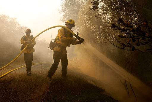 Santa Paula firefighter Tyler Zeller, right, hoses down a hot spot with the help of Jesse Phillips, Thursday, Oct. 12, 2017, in Sonoma, Calif. Firefighters from across the state have been brought in to help battle the blazers that started Sunday night.