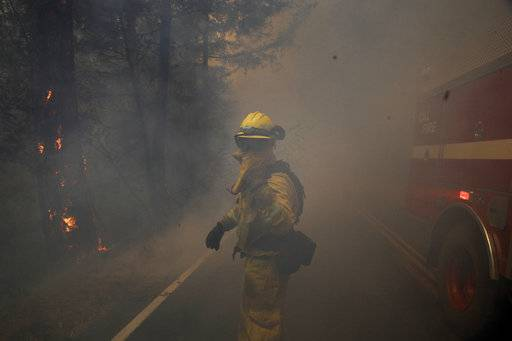 A firefighter gestures to his colleagues as he walks through thick smoke from a wildfire Thursday, Oct. 12, 2017, near Calistoga, Calif.