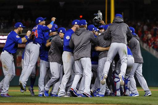 The Chicago Cubs celebrate after beating the Washington Nationals 9-8 to to win baseball's National League Division Series, at Nationals Park, early Friday, Oct. 13, 2017, in Washington. (AP Photo/Pablo Martinez Monsivais)