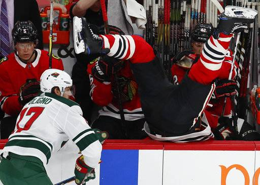Chicago Blackhawks' Brent Seabrook, right, goes over the boards after missing a check on Minnesota Wild's Marcus Foligno during the first period of an NHL hockey game Thursday, Oct. 12, 2017, in Chicago. (AP Photo/Jim Young)