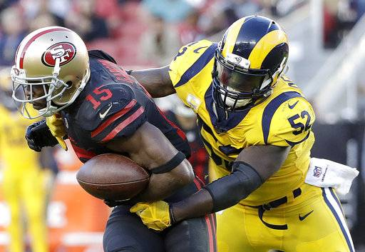 FILE - In this Sept. 21, 2017, file photo, San Francisco 49ers wide receiver Pierre Garcon (15) is tackled by Los Angeles Rams inside linebacker Alec Ogletree (52) during the first half of an NFL football game in Santa Clara, Calif. Ogletree has agreed to a four-year contract extension with the Rams through the 2021 season. The Rams announced the deal Thursday night, Oct, 12, with their top tackler and a key leader on their defense. (AP Photo/Marcio Jose Sanchez, File)