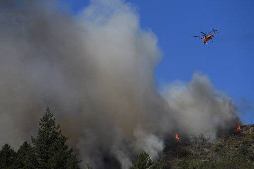 A helicopter flies over a wildfire Thursday, Oct. 12, 2017, near Calistoga, Calif. Officials say progress is being made in some of the largest wildfires burning in Northern California but that the death toll is almost sure to surge. (AP Photo/Jae C. Hong)