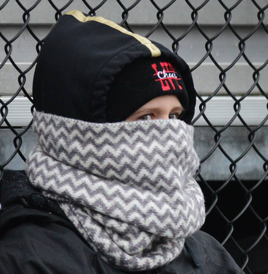 Grayslake North senior Karolina Wytrzyszczewski tries to stay warm while watching the Knights play Belvidere North during round two of the Class 6A football playoffs in Grayslake.
