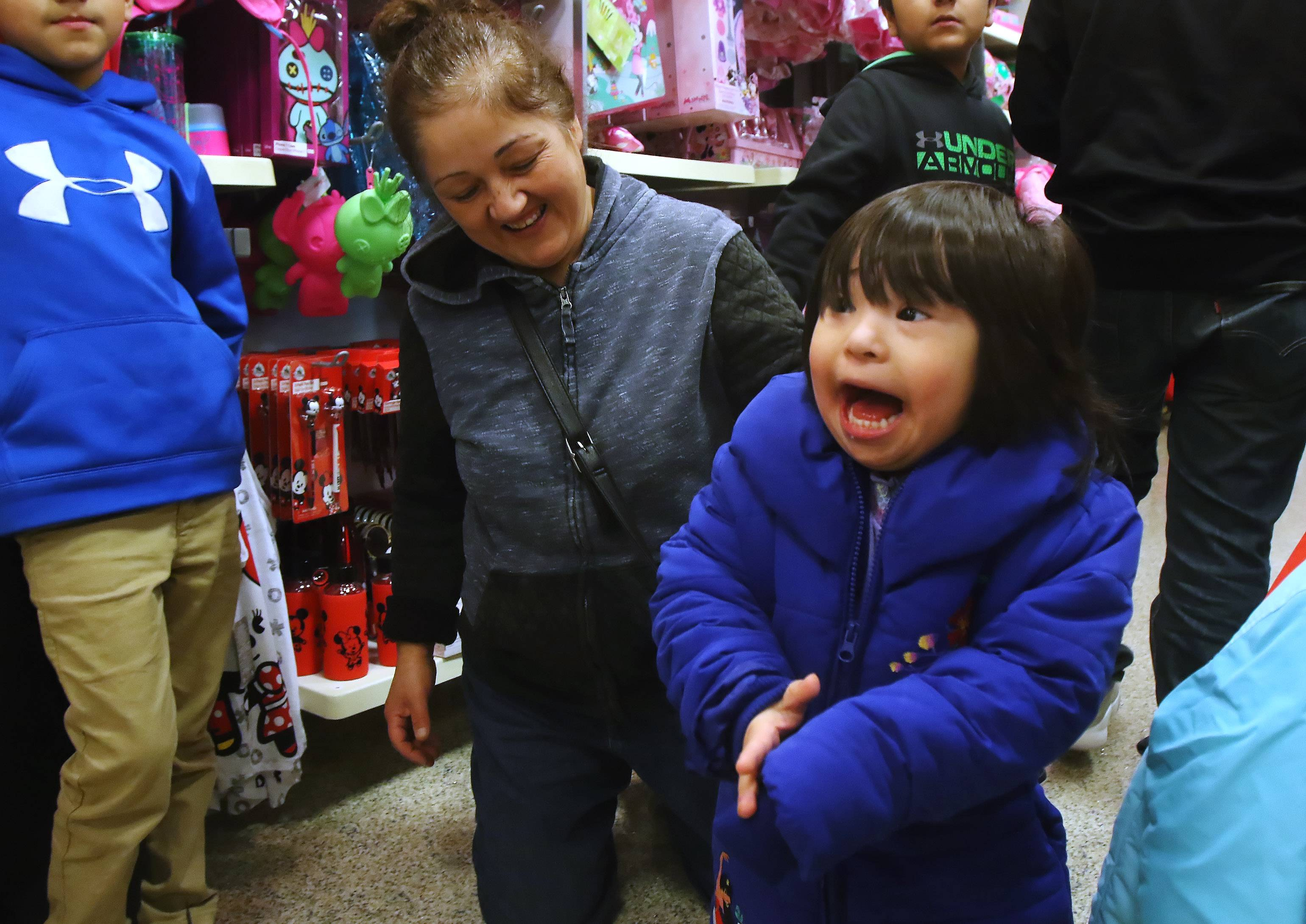Four-year-old Bianca Martinez of Kenosha, Wis. is excited as she shops for clothes and toys with her mom, Rebeca, at the Disney Outlet on Sunday with the help of Make-A-Wish. Bianca, who suffers from Down syndrome and leukemia, was given a shopping experience at Gurnee Mills, visiting Build-A-Bear Workshop, Toys R Us Outlet, the Lego Store and other shops.