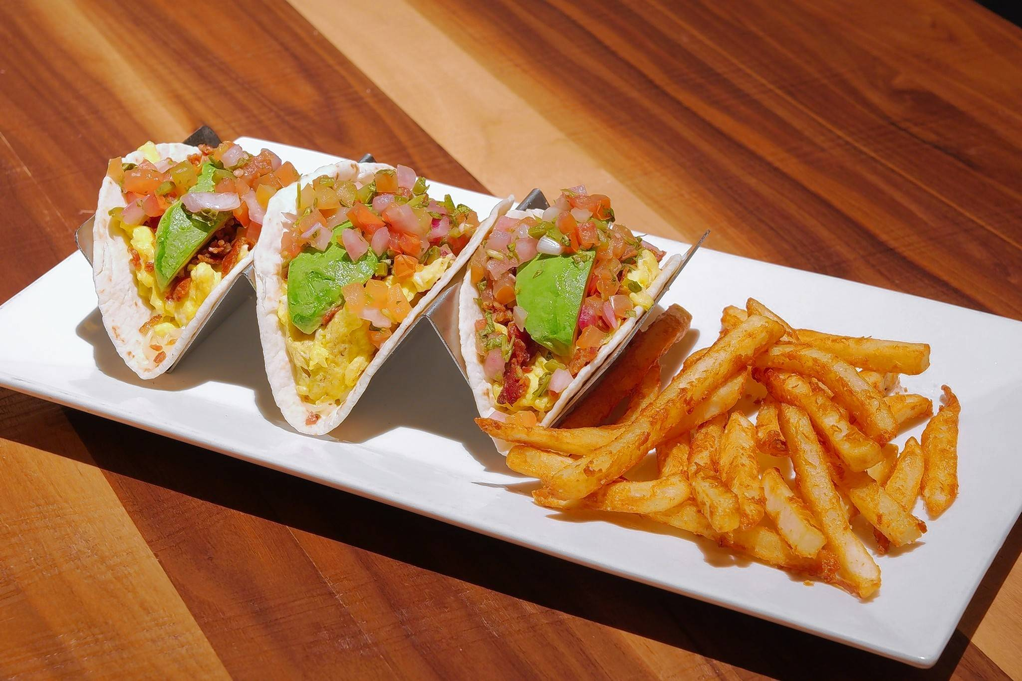 The Draft Room's breakfast tacos are filled with scrambled eggs, bacon, cheddar, avocado and pico de gallo.