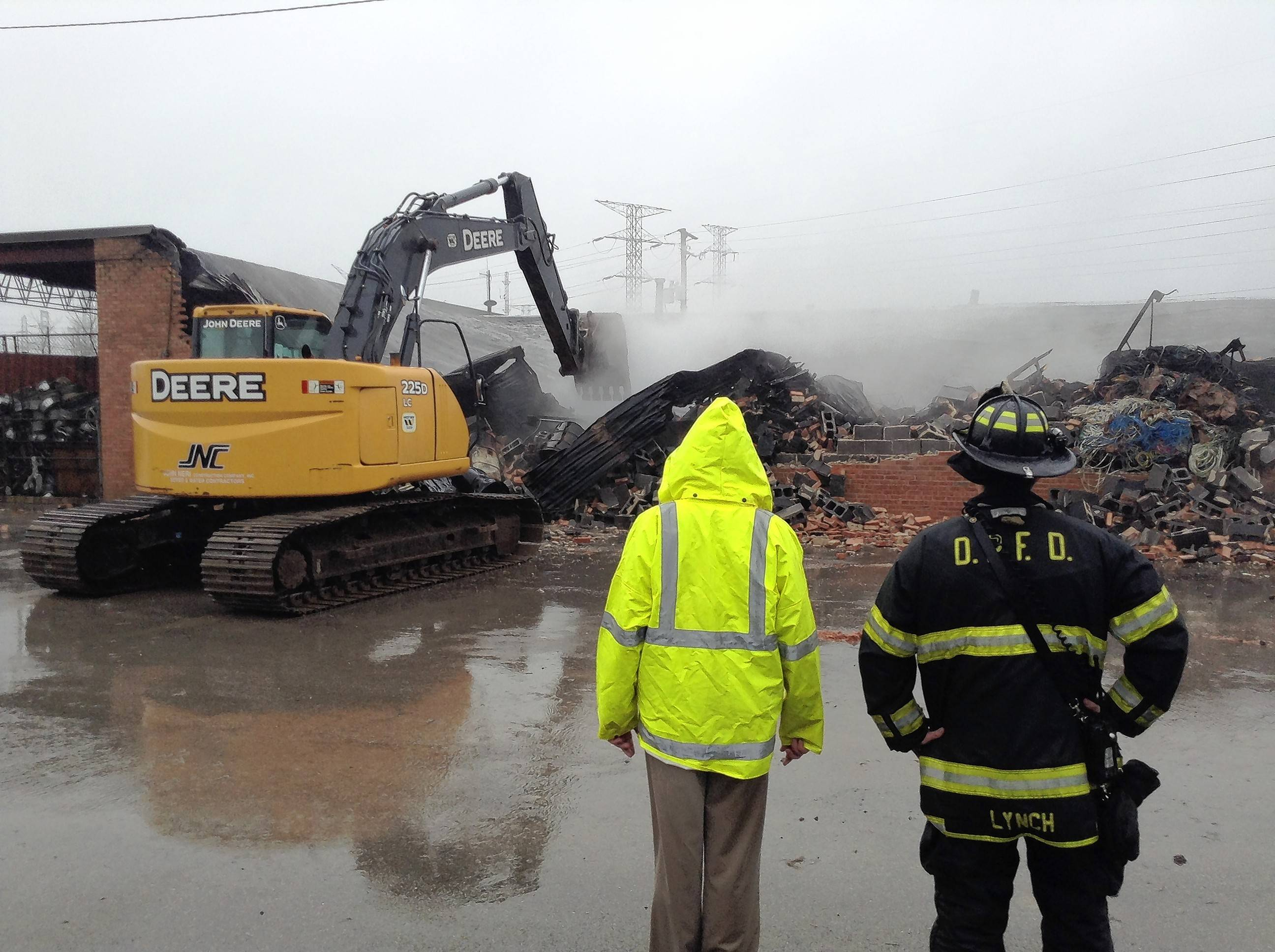 A backhoe rips apart the collapsed roof of a scrap metal recycling facility Thursday in Des Plaines, where a massive fire occurred overnight.