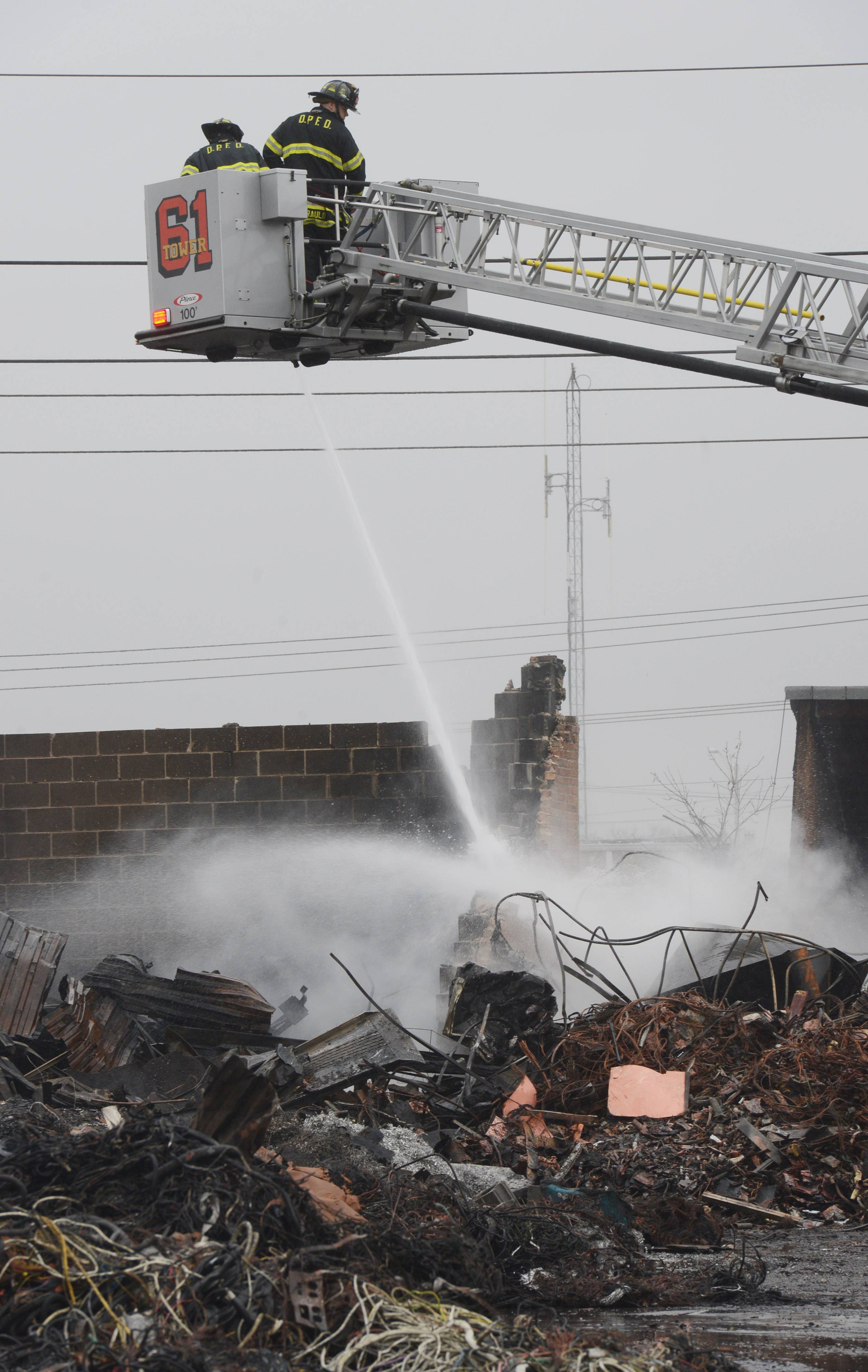 Firefighters spray water on the smoldering remnants of Maine Scrap Metal's factory Thursday in Des Plaines.