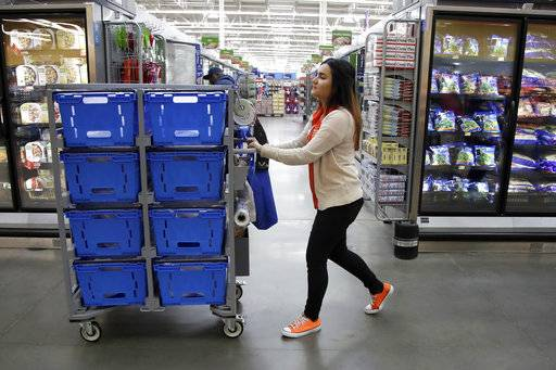 In this Thursday, Nov. 9, 2017, photo, Laila Ummelaila, a personal shopper at the Walmart store in Old Bridge, N.J., pushes a cart with bins as she shops for online shoppers. On Thursday, Jan. 11, 2018, Walmart announced it is boosting its starting salary for U.S. workers to $11 an hour, giving a one-time $1,000 cash bonus to eligible employees and expanding its maternity and parental leave benefits.
