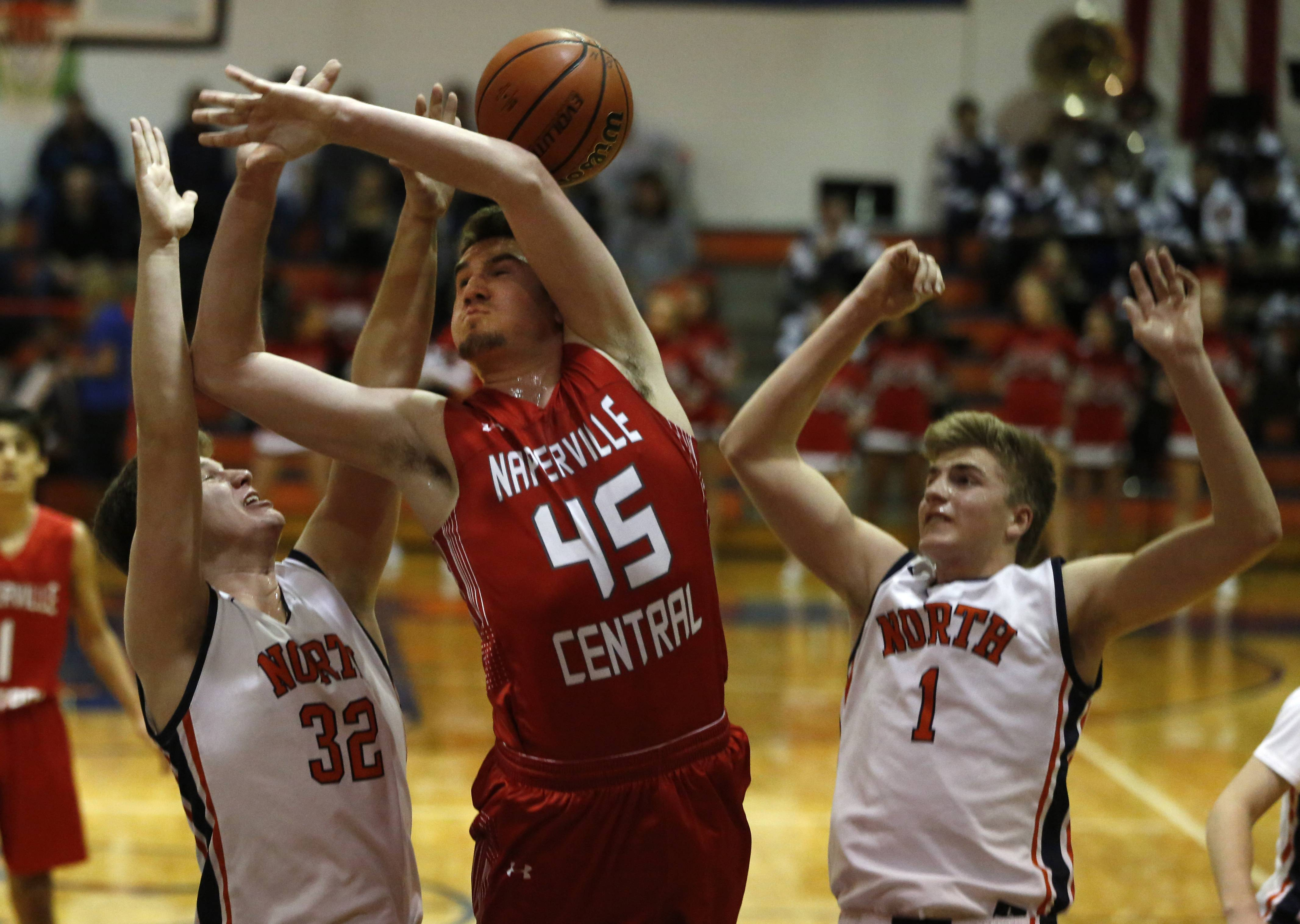 Naperville Central's Benjamin Wolf (45) battles Naperville North's Chris Johnson (32) and Tom Welch (1).