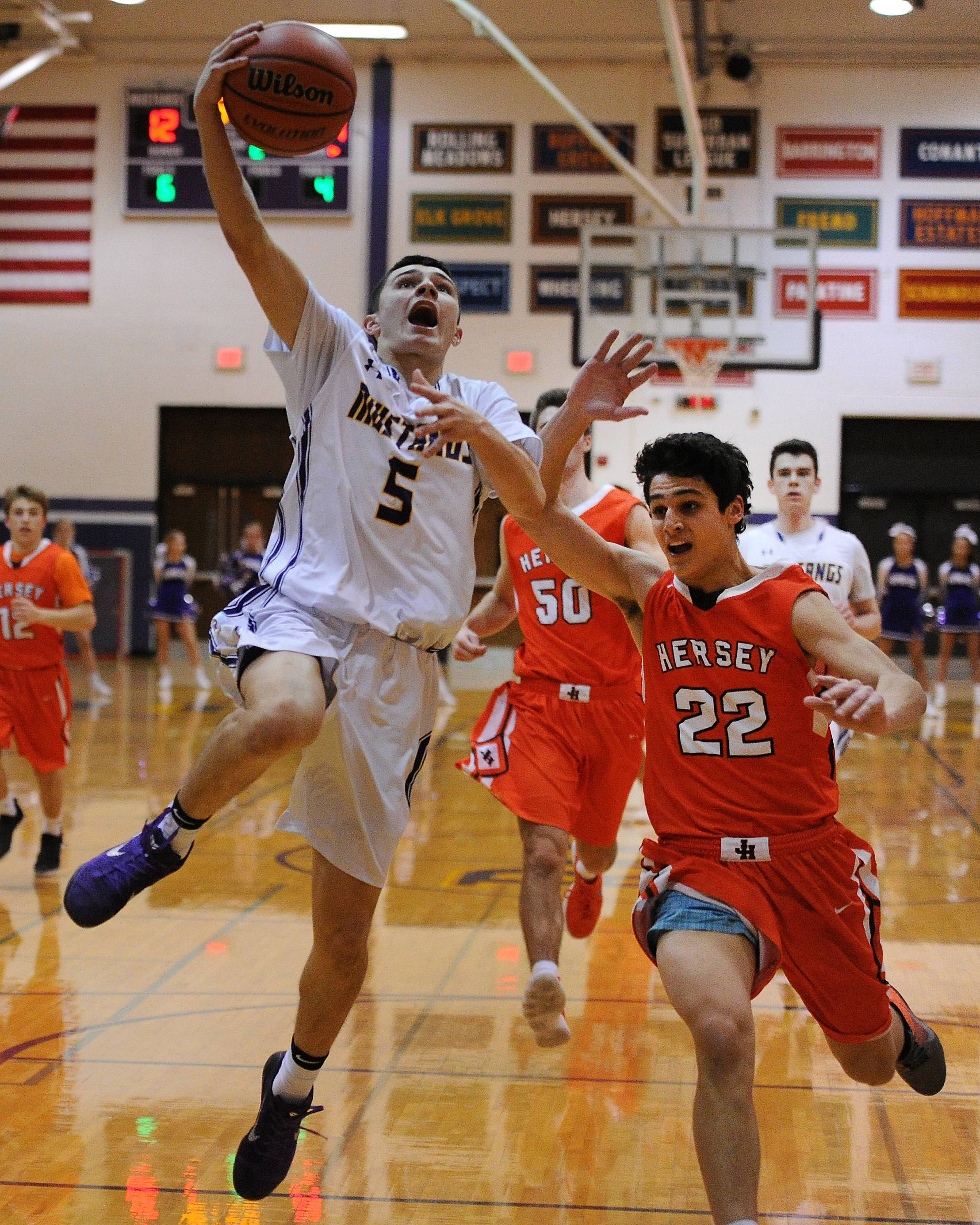 Rolling Meadows' Willis Goodwin delivers two despite pressure from Hersey's Jace Coffaro in the first half of boys varsity basketball at Rolling Meadows on Friday.