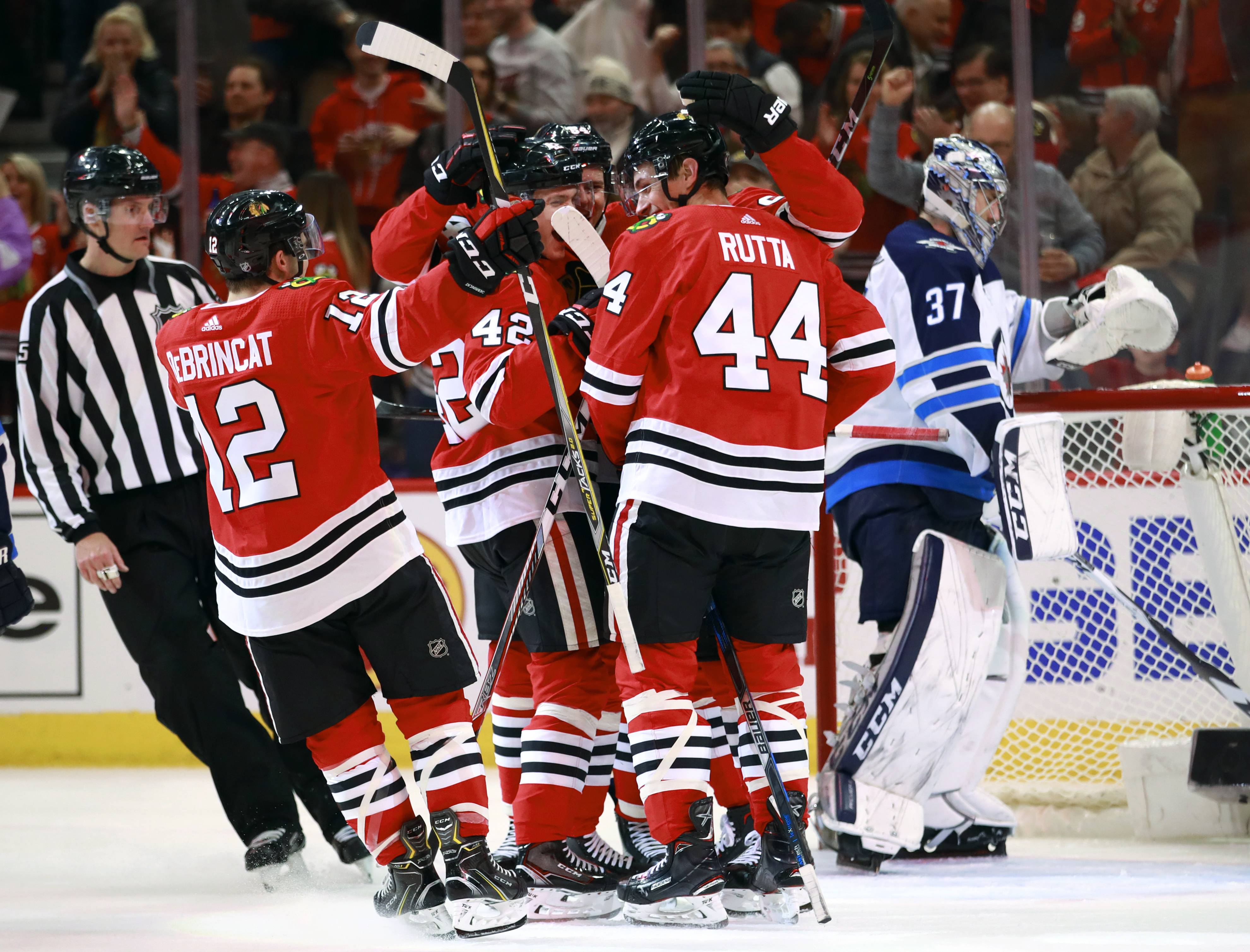 Blackhawks defenseman Jan Rutta celebrates with teammates after his goal as Winnipeg Jets goaltender Connor Hellebuyck (37) stands in the net during the second period on Friday night at the United Center in Chicago.