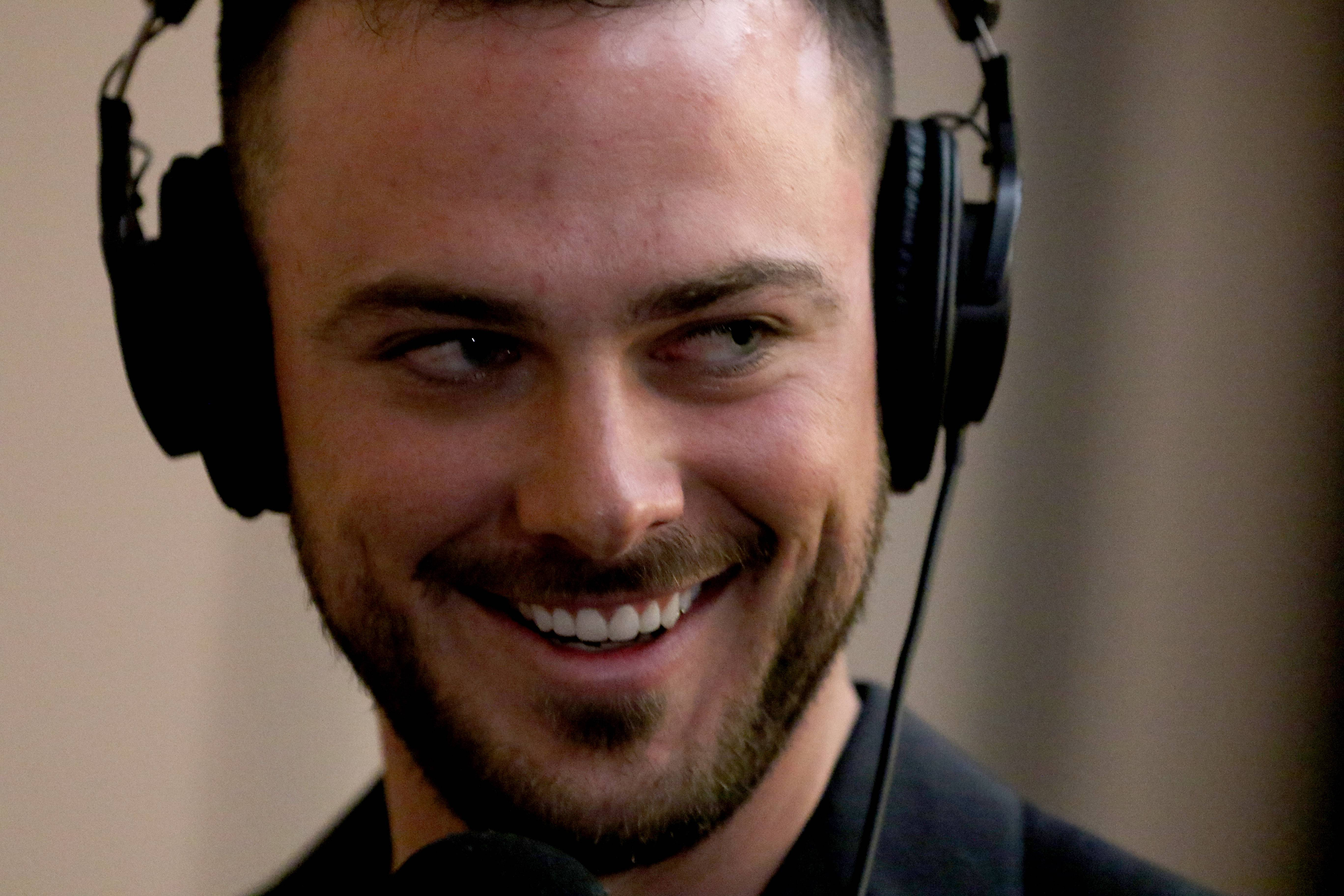 Kris Bryant smiles while doing a radio interview during opening night of the 33rd annual Cubs Convention in Chicago Friday night.