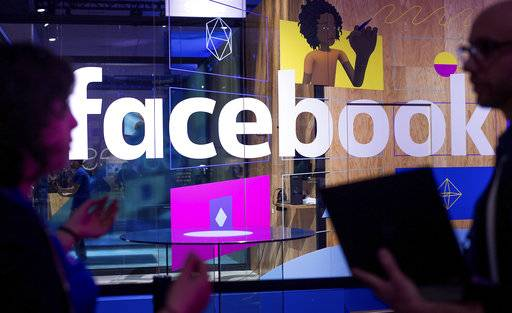"FILE - In this April 18, 2017, file photo, conference workers speak in front of a demo booth at Facebook's annual F8 developer conference in San Jose, Calif. Facebook said Thursday, Jan. 11, 2018, that it is tweaking what people see to make their time on it more ""meaningful.� The changes come as Facebook faces criticism that social media can make people feel depressed and isolated. (AP Photo/Noah Berger, File)"
