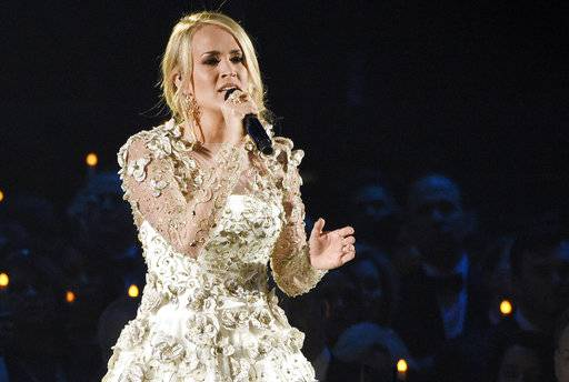 "FILE - In this Wednesday, Nov. 8, 2017, file photo, Carrie Underwood performs ""Softly and Tenderly"" during an In Memoriam tribute at the 51st annual CMA Awards at the Bridgestone Arena in Nashville, Tenn. Underwood teamed up with Ludacris to co-write a new song ""The Champion,� which will be the opening video for the Super Bowl on Feb. 4 airing on NBC. The song, which was also written by country songwriters Brett James and Chris DeStefano, was released Friday, Jan. 12, 2018. (Photo by Chris Pizzello/Invision/AP, File"