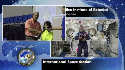In this image from video made available by NASA, astronaut Joe Acaba, right, aboard the International Space Station, takes questions from students at the Puerto Rico Institute of Robotics in San Juan, Puerto Rico on Friday, Jan 12, 2018. One student asked how Puerto Rico looked from space after Hurricane Maria struck in September 2017. Acaba says the first thing he noticed was the lack of electricity, making the island almost impossible to see at night. (NASA via AP)
