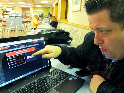 In this Nov. 21, 2013, photo, Joseph Brennen tries to log on to a gambling site while at a highway rest stop in Egg Harbor Township N.J., on the first night of New Jersey's Internet gambling test. On Thursday, Jan. 11, 2018, New Jersey lawmakers from both political parties urged the U.S. Justice Department to keep internet gambling legal, responding to a request from two U.S. senators to reverse a 2011 ruling that internet gambling does not violate federal law. (AP Photo/Wayne Parry)