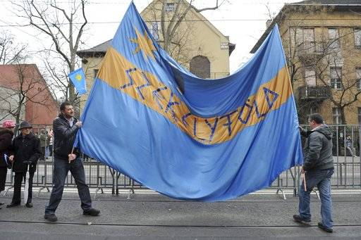 "FILE - A file photo taken on March 10, 2013, shows participants holding a huge Sekler flag in front of the Romanian embassy during a demonstration for Szekler autonomy in Budapest, Hungary. Hungary's foreign minister says provocative comments by Romania's prime minister about autonomy efforts by Szeklers, a group of ethnic Hungarians in Romania, are ""totally unacceptable"" and ""unworthy of the 21st century."" Romanian Prime Minister Mihai Tudose said Wednesday Jan. 10, 2018, on Realitatea TV that ""if the Szekler flag flies on institutions there, they'll all fly next to the flag."" (Lajos Soos/MTI via AP,file)"