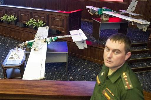 A Russian officer stands next to drones that attacked the Russian air base in Syria and were captured by the Russian military are displayed at a briefing in the Russian Defense Ministry in Moscow, Russia, Thursday, Jan. 11, 2018. Saturday's, Jan.6, 2018 raid against the Hemeimeem air base and a Russian naval facility in Tartus involved 13 drones, seven of the drones were shot down by air defense systems and the remaining six were forced to land, according to the Russian Defense Ministry. (AP Photo/Pavel Golovkin)