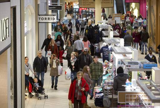 FILE - In this Tuesday, Dec. 26, 2017, file photo, shoppers take advantage of discounts and slashed post-Christmas prices at Valley View Mall in Roanoke, Va. The National Retail Federation said Friday, Jan. 12, 2018, that holiday sales reached $691.9 billion as shoppers stepped up their spending in the wake of a better economy. (Erica Yoon/The Roanoke Times via AP, File)