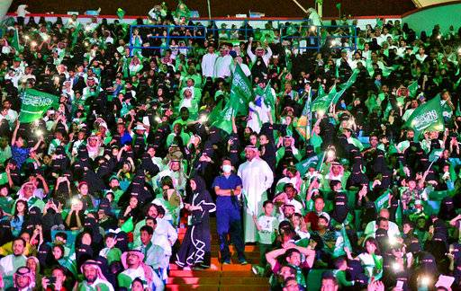 "FILE - In this Sept. 23, 2017 file photo released by Saudi Press Agency, SPA, Saudi men and women attend national day ceremonies at the King Fahd stadium in Riyadh, Saudi Arabia. Saudi women will for the first time be allowed to enter a sports stadium on Friday, Jan. 12, 2018, to watch a soccer match between two local teams - though they will be segregated from the male-only crowd with designated seating in the so-called ""family section."" The move is Saudi Arabia's first social reform planned for this year granting women greater rights. (Saudi Press Agency via AP, File)"