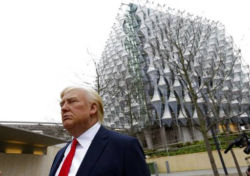 The Madame Tussauds wax figure of US President Donald Trump is seen outside the new US Embassy in Nine Elms in London, Friday, Jan. 12, 2018. President Donald Trump says he canceled upcoming trip to London because he doesn't like the choice of a new embassy. Some British lawmakers have questioned whether Trump would be welcome in London after some of his earlier comments. (AP Photo/Alastair Grant)