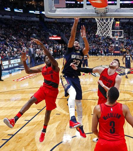 New Orleans Pelicans forward Anthony Davis (23) shoots between Portland Trail Blazers forward Al-Farouq Aminu (8), center Jusuf Nurkic (27) and guard CJ McCollum (3) during the second half of an NBA basketball game in New Orleans, Friday, Jan. 12, 2018. The Pelicans won 119-113. (AP Photo/Gerald Herbert)