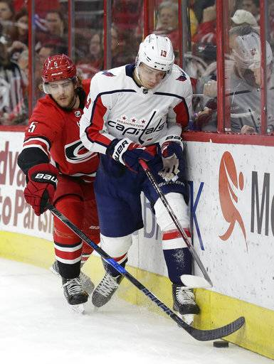 Washington Capitals' Jakub Vrana (13), of the Czech Republic, and Carolina Hurricanes' Noah Hanifin (5) skate for the puck during the first period of an NHL hockey game in Raleigh, N.C., Friday, Jan. 12, 2018. (AP Photo/Gerry Broome)