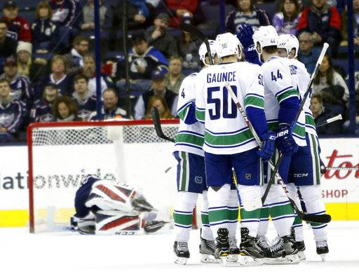 Vancouver Canucks players celebrate their goal against Columbus Blue Jackets' Sergei Bobrovsky, of Russia, during the second period of an NHL hockey game Friday, Jan. 12, 2018, in Columbus, Ohio. (AP Photo/Jay LaPrete)