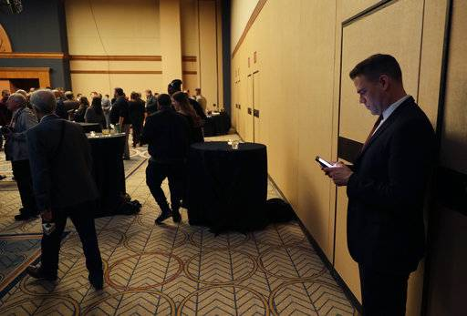 Chicago Cubs president of baseball o right,perations Theo Epstein, checks his phone during the Cubs' annual baseball convention Friday, Jan. 12, 2018, in Chicago. (AP Photo/Charles Rex Arbogast)