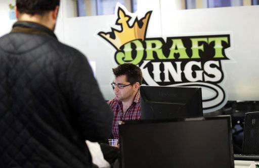 In this Thursday, Jan. 11, 2018 photo, employees work at the DraftKings office in Boston. The leading daily fantasy sports company has launched a new sports game that lets users hone in on a single NFL football playoff game, which has some gambling experts wondering if the contest inches the industry closer to the territory of sports betting that remains illegal in most of the United States. (AP Photo/Charles Krupa)