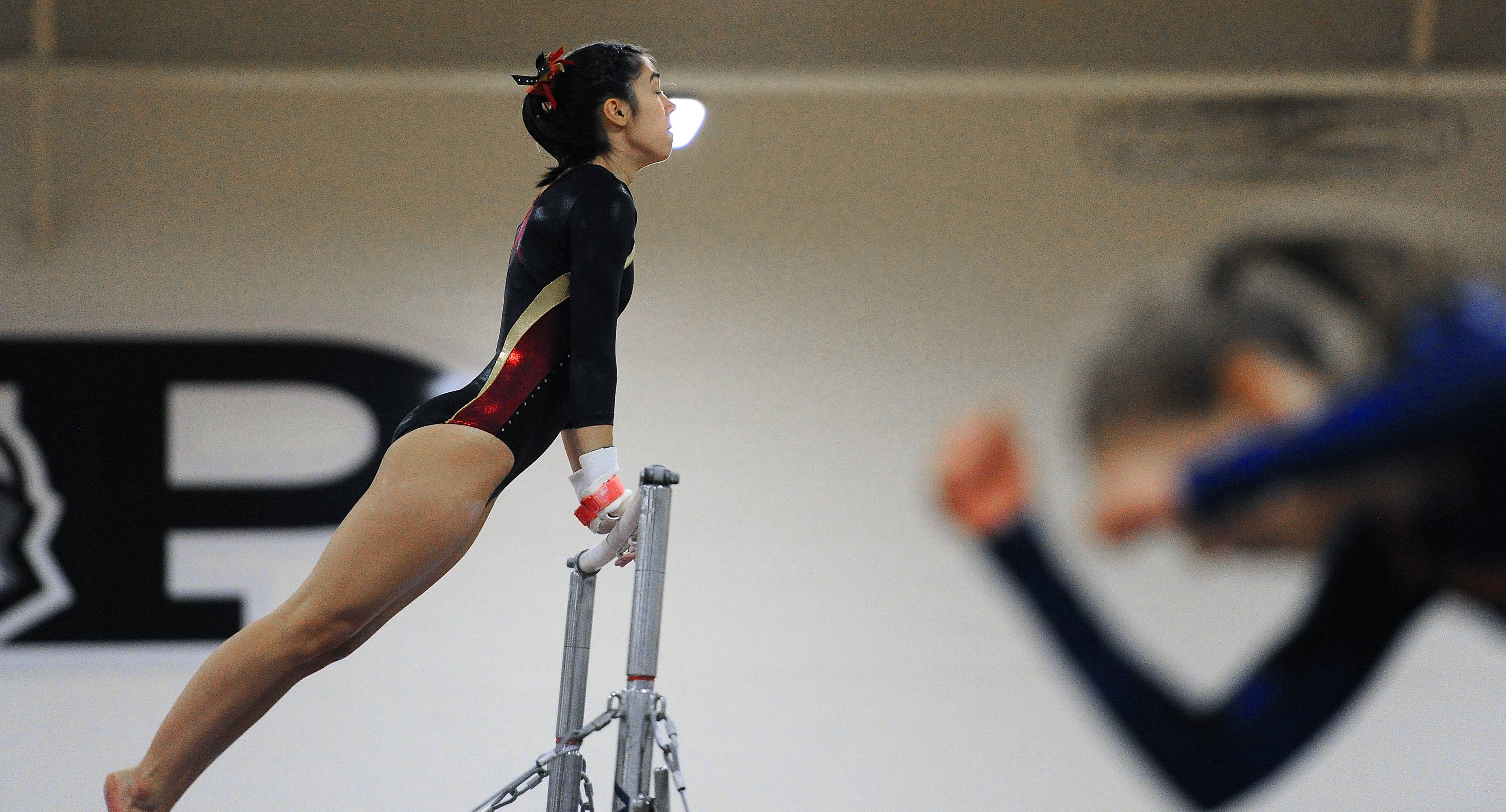 Schaumburg's Chalisa Kulprathipanja competes on the uneven parallel bars at Prospect on Saturday.