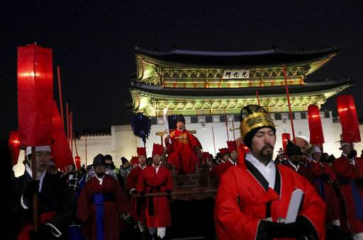 A torch bearer wearing traditional costumes carries the torch during the Olympic Torch Relay in Seoul, South Korea, Saturday, Jan. 13, 2018. South Korea said Saturday that North Korea proposed that their talks next week address a North Korean art troupe's visit to the Pyeongchang Winter Olympics in the South, rather than the participation of the nation's athletes.