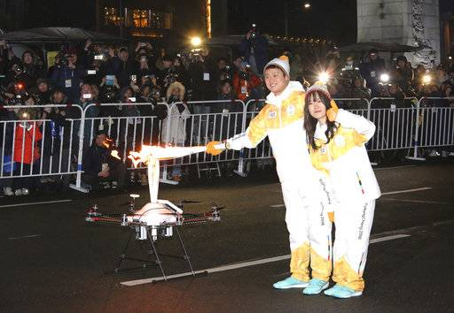 Torch bearers pose as they pass the Olympic flame to a drone during the Olympic Torch Relay in Seoul, South Korea, Saturday, Jan. 13, 2018. South Korea said Saturday that North Korea proposed that their talks next week address a North Korean art troupe's visit to the Pyeongchang Winter Olympics in the South, rather than the participation of the nation's athletes.