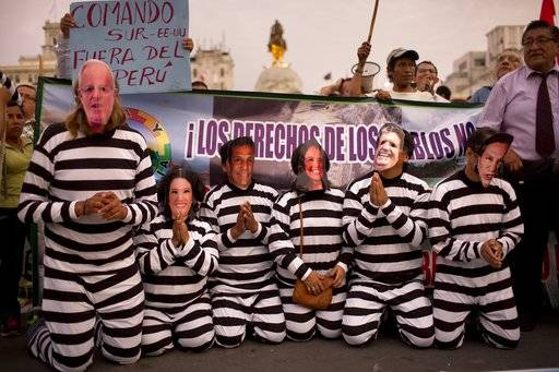 FILE - In this Jan. 19, 2017 file photo, people wearing masks of Peruvian politicians pretend to be prisoners during a protest calling for justice after the Odebrecht corruption scandal in Lima, Peru. Pope Francis frequently rails against corruption during his foreign trips, calling it more insidious than sin and a plague that harms the poorest the most.