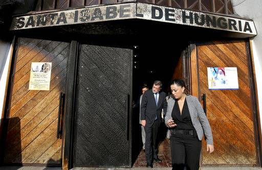 "Deputy Interior Secretary Aleuy Mahmud, center, exits the Santa Isabel de Hungria Catholic Church, past a door damaged in an overnight fire-bomb attack, in Santiago, Chile, Friday, Jan. 12, 2018. On the eve of a papal visit, vandals fire-bombed three churches in the Chilean capital and warned in a leaflet that ""the next bombs will be in your cassock"", an unprecedented threat against the pope and a violent start to what were already expected to be the first-ever protests against Pope Francis on a foreign trip."