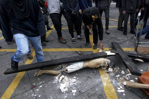 FILE - In this June 9, 2016 photo, a group of masked men stand destroy a crucifixion of Jesus Christ after they removed it from a Catholic church, in Santiago, Chile. The Vatican agreed to the Jan. 15-18 Chile papal visit knowing well that the local church had lost much of the moral authority it earned during the Pinochet dictatorship. But now, the Catholic Church has been largely marginalized, criticized as out-of-touch with today's secular Chile and discredited by its botched handling of a notorious pedophile priest.